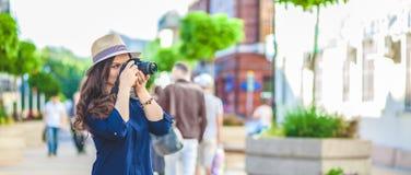 Le beau touriste de femme marchant sur la rue avec un appareil-photo et prend le concept de bannière de photos explorant la ville Photographie stock