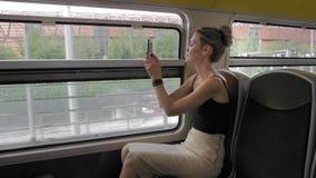 Le beau touriste féminin caucasien monte un train et prend des photos de la zone industrielle de la ville Dans la fen?tre clips vidéos