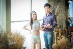 Le beau ventre enceinte très heureux de jeune homme et de femme écoutent t Photo stock