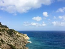 Le beau vew de mer et de roches au-dessus de l'horizon à Cala Llonga aboient, je photos stock