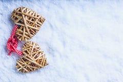 Le beau vintage deux a enlacé les coeurs flaxen beiges attachés ainsi qu'un ruban sur la neige blanche Amour et concept de jour d Photo libre de droits