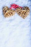 Le beau vintage deux a enlacé les coeurs flaxen beiges attachés ainsi qu'un ruban sur la neige blanche Amour et concept de jour d Photographie stock