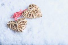 Le beau vintage deux a enlacé les coeurs flaxen beiges attachés ainsi qu'un ruban sur la neige blanche Amour et concept de jour d Images libres de droits