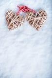 Le beau vintage deux romantique a enlacé les coeurs flaxen beiges attachés ainsi qu'un ruban sur un fond blanc d'hiver de neige Image libre de droits