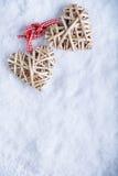 Le beau vintage deux romantique a enlacé les coeurs flaxen beiges attachés ainsi qu'un ruban sur un fond blanc d'hiver de neige Photos libres de droits
