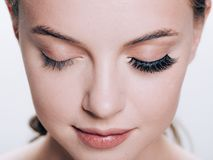 Le beau visage de femme avec des cils fouette l'extension avant et après que le maquillage naturel de peau saine de beauté ait fe photographie stock libre de droits