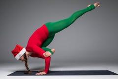 Le beau yoga de pratique en matière de femme de yoga pose sur le fond gris Photo stock