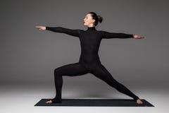 Le beau yoga de pratique en matière de femme de yoga pose sur le fond gris photographie stock libre de droits