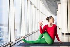 Le beau yoga de pratique en matière de femme de yoga pose sur le fond gris photos libres de droits
