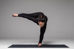 Le beau yoga de pratique en matière de femme de yoga pose sur le fond gris images libres de droits