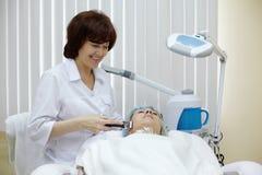 Le Beautician traite la peau de visage du patient image stock