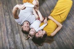 Le beaux jeunes père, mère et fille heureux de famille sont doi Image stock