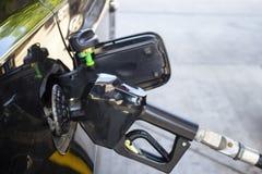 Le bec de pompe à gaz a injecté le gaz dans le réservoir de gaz du véhicule noir avec le fond brouillé photos stock