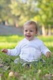 Le behandla som ett barn-pojke sammanträde på gräs Arkivbilder
