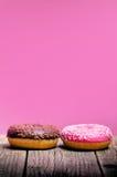 Le beignet avec arrose sur une table en bois et un fond rose Deux types de butées toriques Gâteau et bonbon Détail de nourriture  Photo libre de droits