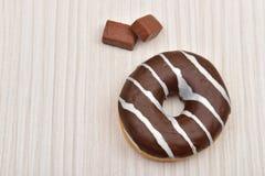 Le beignet de chocolat avec des rayures et le morceau de chocolat sur le blanc courtisent photo libre de droits