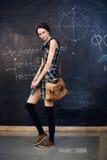 Le bel étudiant se tient au tableau noir Photo stock