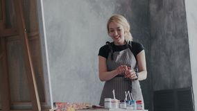 Le bel artiste féminin heureux fait ce qu'elle aime Elle se tient devant le chevalet et la peinture de mélanges Le concept de illustration de vecteur