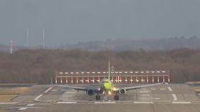 Le bel avion de passagers de vert jaune débarque sur la piste d'atterrissage à l'aéroport banque de vidéos