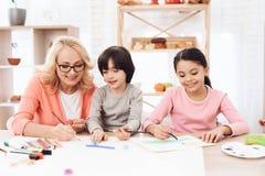 Le bel egrandmother enseigne des petits-enfants à dessiner Aspiration d'enfants avec des peintures Images libres de droits