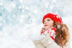 Le bel enfant étire sa main pour attraper les flocons de neige en baisse Photos stock