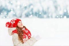 Le bel enfant étire sa main pour attraper les flocons de neige en baisse Photographie stock