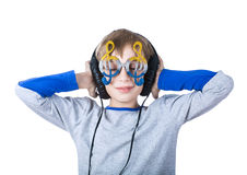 Le bel enfant blond élégant portant de grands écouteurs professionnels et lunettes drôles écoute la musique image libre de droits