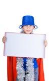 Le bel enfant heureux utilisant le chapeau bleu de partie tient un petit conseil blanc rectangulaire Image libre de droits