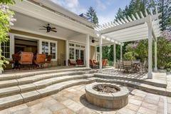 Le bel espace extérieur de patio de plate-forme avec la pergola dinante blanche image libre de droits
