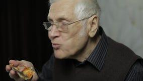 Le bel homme plus âgé en verres mange de la pizza Montre que combien savoureux la pizza est banque de vidéos