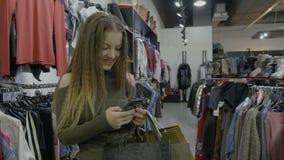 Le bel influencer social de media faisant ses achats reçoit des messages et des réponses à ses fans après la signalisation d'un s banque de vidéos