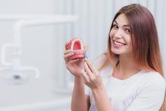 Le bel orthodontiste de docteur te montre comment entretenir vos dents photos stock