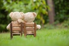 Le bel ours de nounours du brun deux se reposent sur la chaise en bois, pendant le matin, Photos stock