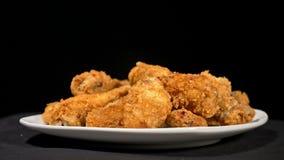 Le belle ali di pollo cucinate succose fresche fresche nell'impanare girano sulla piattaforma girevole Ale di pollo fritte spante archivi video