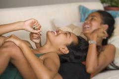 le belle amiche gay asiatiche felici coppia la risata allegra insieme divertendosi a casa lo strato del sofà che stringono a sé e fotografie stock