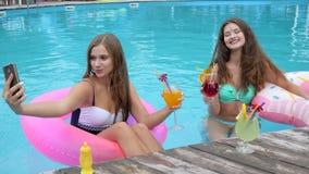 Le belle amiche sull'anello gonfiabile fanno il selfie in stagno, ragazze ai costumi da bagno con i cocktail in mani fotografate stock footage