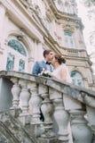 Le belle coppie della persona appena sposata nell'amore hanno momento romantico sulle scale antiche al vecchio palazzo austriaco fotografie stock