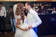 Le belle coppie della persona appena sposata in primo luogo ballano al ricevimento nuziale circondato da fumo e dal blu Fotografie Stock