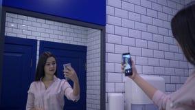 Le belle donne è fotografata sulla condizione dello smartphone davanti allo specchio in toilette stock footage