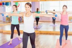 Le belle donne che fanno la forma fisica si esercitano con peso in mani Immagini Stock