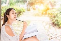 Le belle donne che smilling e carta da lettere sulla terra nel parco Immagini Stock