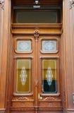 Le belle doppie porte di entrata antiche di legno con i rettangoli di vetro con bianco hanno dipinto gli ornamenti floreali fotografia stock