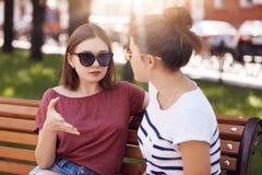 Le belle due giovani donne in tonalità d'avanguardia, discutono qualcosa, parlano con i gesti, si siedono sul banco fuori, recrea fotografie stock libere da diritti