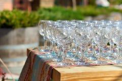 Le belle file di glassestwo dei bicchieri di vino della tavola di festa dei vetri su una tavola con tableclothglasses bianchi sul Fotografia Stock
