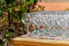 Le belle file di glassestwo dei bicchieri di vino della tavola di festa dei vetri su una tavola con tableclothglasses bianchi sul Fotografia Stock Libera da Diritti