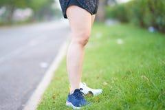 Le belle gambe della ragazza di sport stanno sull'erba di bordo in befo di mattina Immagine Stock Libera da Diritti