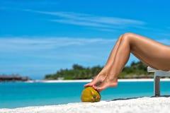 Le belle gambe delle donne sulla noce di cocco sulla spiaggia, backgro blu del mare Fotografie Stock