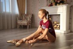 Le belle gambe di giovane ballerina che mette sopra pointe calza la seduta sul pavimento di legno Pratica di balletto Bei piedi g Immagini Stock