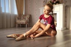Le belle gambe di giovane ballerina che mette sopra pointe calza la seduta sul pavimento di legno, vista superiore con lo spazio  Immagine Stock