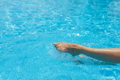 Le belle gambe femminili bruciate, spruzza, la chiara acqua dello stagno del turchese immagine stock
